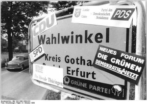 Place-name sign covered with stickers of the parties standing for election in the 1990 federal elections